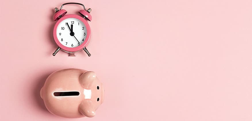 Aerial view of piggy bank and old school alarm clock on a pink background.
