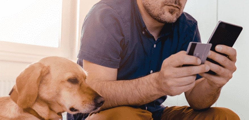 man with dog by his side updates his credit card on the Scout for Pet Owners app.