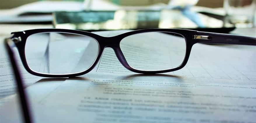 A pair of eyeglasses sitting on top of a legal document.
